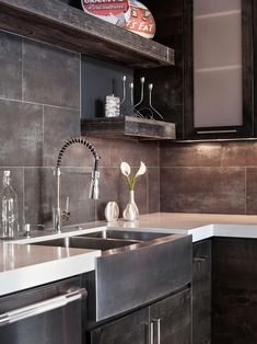 A modern farmhouse sink ties together the rustic elements of this contemporary kitchen, including barn wood floating shelves and knotty alder cabinets.