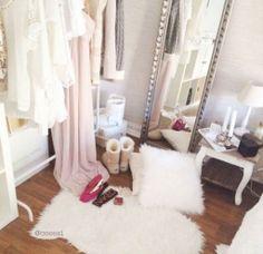 Garment rack, furry rug, body mirror, furry pillows, little table for makeup.