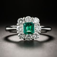 Modestly proportioned (.45 carat), but as gorgeous green as you can possibly imagine, a gemmy Colombian emerald is framed by sparkling high-color round brilliant-cut diamonds (totaling .80 carat) in this classic and pristine estate jewel. Crafted in gleaming platinum, 3/8 inch, currently ring size 5 3/4.