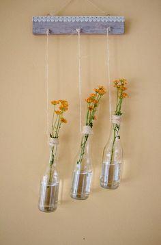 Conjunto de 3 vasos de flores feito em garrafa, num suporte de madeira R$ 499,00