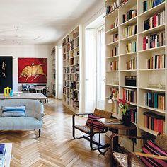 Blue pinstripe couch, bookshelves.