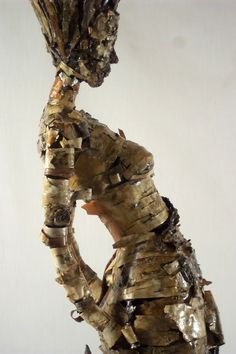 """New Skin by Becky Grismer. New Skin represents the common characteristic of both trees and humans naturally exfoliating their skin. The sculpture is made entirely from birch and hickory shag bark. Both are trees that naturally shed their bark or """"skin""""."""
