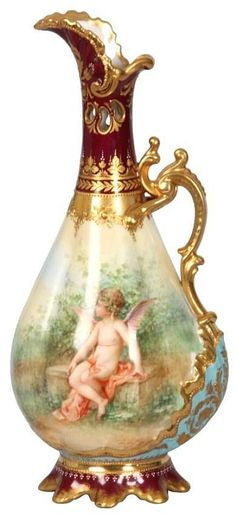 Royal Vienna Porcelain Ewer. Teardrop gourd form with reticulated bottle neck, flowing spout and fancy gilt handle; decorated on the front and back with winged putti figures, maroon decorated foot and top with gilt and enamel highlights. Signed with the beehive mark on the bottom, has a small flat chip on one foot, no breaks or repairs to the spout or handle, no hairlines. 10 in. high.