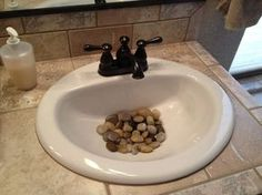 River rocks in the bathroom sink. A little feng shui but a neat way to decorate too! Love this idea.