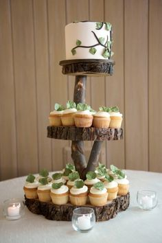 Wedding cupcakes and a cutting cake displayed on wooden tree slices and elevated by tree limbs in a cupcake tower.