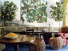 "In this Palm Beach, Florida, dining room Bilhuber strove to conjure ""a magical, sprawling Surrealist perspective."" Bilhuber challenges the viewer to see the panoramic wallpaper anew, pairing it with a Chester Arnold painting (""a super-graphic blowup""), and brings the paper's spirit into the third dimension with potted lemon trees."