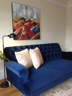 Navy blue sofa in velvet, large art piece, Karastan rug with delicate pattern and apothecary, vintage lamp