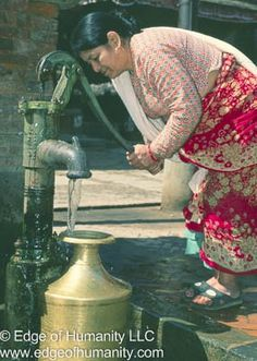 Woman pupping water from a well in Nepal.