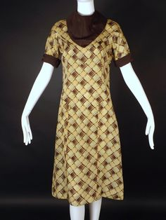 Early 1930s day dress in yellow, green and brown silk plaid. Brown bib collar and cuffs. Button closures down the back. The silk feels very dry. Missing one button. Scattered light staining on the fro