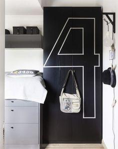 Garderoben är ett Pax-skåp från Ikea som fått en rejäl makeover med svart färg och washitejp. Siffran fyra på klädskåpet bryter av mot den stora mörka ytan och utgör en grafisk detalj i rummet. I skåpet förvaras kläder och leksaker i korgar. Vägglampan är ett hemmabygge gjort av en konsol och en textilsladd med en stor frostad lampa.