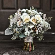 Winter wedding bouquet -- Roses, fir branches, dusty miller, brunia berries, eucalyptus, pine cones