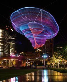 Janet Echelman suspend des filets en l'air et les illumines de couleurs la nuit tombée, sa prochaine oeuvre sera un filet similaire de plus de 200m de long suspendu dans le ciel de Vancouver le mois prochain.