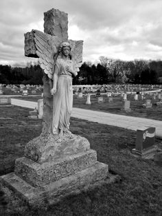 ThisGranite Statue of Angel Standing With Her Wings Outstretched in Front of a Large Cross Can Be Found at St. Mary's Cemetery in Putnam, CT
