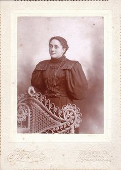 This is an original vintage photograph from the 1800s. It shows a Vicorian woman in pinch-nose spectacles posing with an ornate wicker chair. The photo was taken in Reading, Pa.