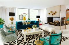 In this colorful, Hollywood Regency style living room, a velvety, turquoise sofa, black and white patterned rug, and golden accents complement one another.