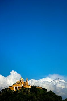 between the volcano clouds - Iglesia de los Remedios on top of the pyramid in Cholula, Mexico