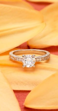This sought after vintage inspired engagement is adorned with an engraved scroll pattern on the top and sides of the band