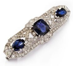 A sapphire and diamond brooch, 1930s The openwork cartouche mounted with a central cushion-shaped sapphire weighing 7.38 carats, flanked by a pair of drop-shaped sapphires, set throughout with single-cut diamonds, drop-shaped sapphires approximately 6.00 carats total, diamonds approximately 2.00 carats total, mounted in platinum, width 6.0cm