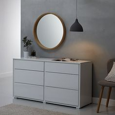 This chic circular wall mirror is a masterpiece of simple Scandinavian design. The mirror's solid oak frame is backed by a comb hanging fitting, making it easy to mount in a living room or hallway.