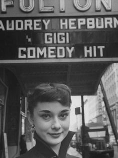 Actress Audrey Hepburn standing beneath Fulton Theatre marquee, which features her name over currently running Broadway show Gigi, which she is starring in. Circa 1951.