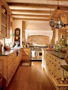 I will be needing a good kitchen. :) Earth tones prevail in this open kitchen that looks as if it's been in place for centuries. Open shelving, naturally finished cabinets, and a pot rack over the center island provide abundant storage.