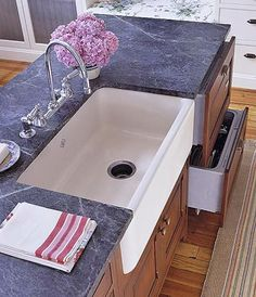 Soapstone Counter and Farmhouse Sink- Add a farmhouse sink to a kitchen island to increase the hardworking areas of your kitchen. The soapstone countertop surrounds the deep-basined apron-front sink. Dishwasher drawers in the island offer modern convenience.