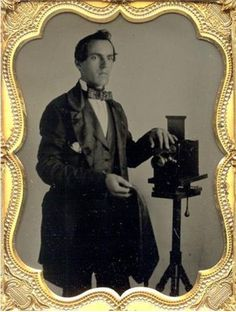ca. 1850-60's, [ambrotype portrait of a long-fingered daguerreotypist with a Lewis-type camera]  via Be-Hold Fine Photographs
