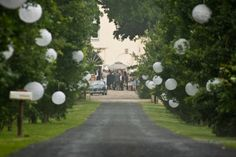 Entree van een bruiloft versiert met witte lampionnen, maar dan het liefst in verschillende lichte kleurtjes (roze, lichtgroen).