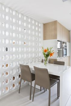 Na cozinha, armários brancos e de madeira se misturam compondo um décor leve e aconchegante. O backsplash com tons de cinza e verde e formas geométricas dão um tom moderninho ao espaço.