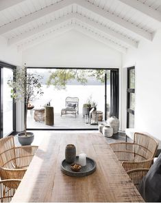 High white washed ceilings, rustic wooden dining table and the most amazing wicker chairs. #openplan #livingspace #lakehouse