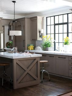 Brown is one of the most comforting colors, so it's a top choice for living rooms and kitchens. The soft brown wood tones in this kitchen make it feel inviting and pleasant. Photo courtesy of Hinkley Lighting