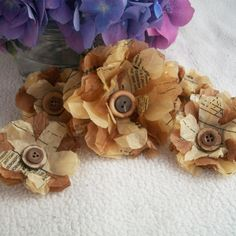 cut flower shaped layers from sewing pattern tissue / add 'distress ink' / clue / stitch button