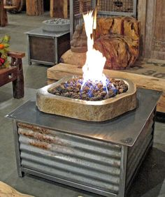 Limited edition square reclaimed steel fire table with natural Andesite Stone fire pit area for burning propane or natural gas. Standard 20lb propane tank fits under table.