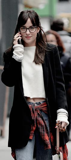 Dakota Johnson rocks a 90s inspired look with flannel tied at the waist, low key denim, and cropped sweater. Add in glasses for good measure.