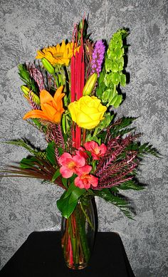 $40 to $50 Everyday Florals - Floral Expressions Inc - Janesville, WI Florist    A brilliant colorful bouquet of day lilies, sunflower, liatris, rose, Alstroemeria lity, and Bells of Ireland, are accented with a variety of foilage and red cattails in this lovely vased arrangement - http://www.floralexpressionsjanesville.com/