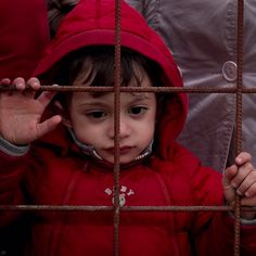 28 Dec 2015 - A little boy stands with adults at a wire fence in the town of Gevgelija, on the border with Greece. In the former Yugoslav Republic of Macedonia, the Government has begun restricting the flow of refugees and migrants on the move, and is allowing only Syrians, Iraqis and Afghans to continue their journey. About 1,000 people are stranded at the main entry point into the former Yugoslav Republic of Macedonia from Greece. © UNICEF/UN03112/Gilbertson VII Photo