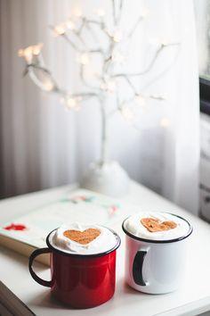 Duas canecas (branca e vermelha) em cima de uma mesa de cabeceira com chantilly e coração de canela.