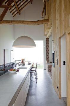 | Grote woning met een lange kookeiland, het karakteristieke van de houten balken komen mooi terug in de keuken zelf |