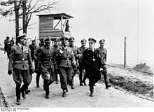 """Himmler and other SS officials visiting a concentration camp in Mauthausen. Unlike Hitler, Himmler paid visits to such camps throughout the war period and guided the process of establishing extermination camps. It is said during one of his visits Himmler """"turned green in the face"""" after brain matter from a executed Jew splattered on his coat. After that incident the Nazi's began to search for new ways to """"deal"""" with Jews and thus the foundation of the infamous gas chambers."""