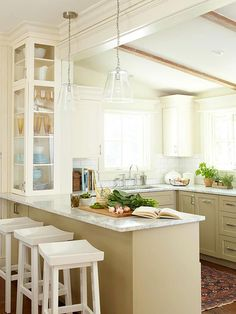 Glass pendants provide extra light over this peninsula without obstructing the view into the living room. A glass cabinet built on top of the peninsula utilizes slim corner space and serves as a china hutch! http://www.bhg.com/decorating/decorating-style/cottage/classic-charm/?socsrc=bhgpin122914shiftingspaceskitchen&page=7