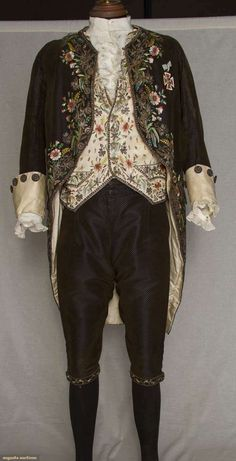 "GENT'S FOUR PIECE FORMAL COURT SUIT, c. 1820. Coat & breeches of dark brown cut/uncut velvet to blue satin ground; coat embroidered in polychrome silk large scale florals, gold metallic cord & crimped foil flowers. Ivoryfaille waistcoat, matching embroidery, CH 40"", FL 26"" (CF turned under 5"" & linen back enlarged); white linen ruffle front shirt, ruffle cuffs, undersleeves,(coat collar & original cuffs removed) fair."