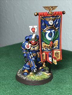 Wielding the Wrath of Guilliman and bearing the newly commissioned banner of the 11th Company founded by Captain Felix Decimus; comes now Ancient Titus Pullo guardian of the Eagle and First Sergeant of the 11th Company. Primaris Marine Ancient #paintingwarhammer