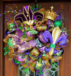 This 28 Mardi Gras wreath is very festive and has lots of sparkle! It adorned with a large mask, purple and gold fleur-de-lis, Mardi Gras beads,