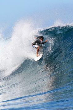 Dennis Tihara riding the waves at Teahupoo, Tahiti