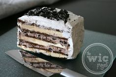 A delicious ice cream cake made with layers of OREO and chocolate frosting and vanilla ice cream sandwiches, topped with Cool Whip.