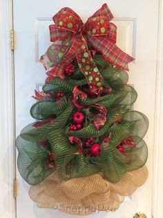 This glittering Christmas tree wreath has been carefully sculpted out of deco mesh, adorned with pomegranate and pinecone picks and complementary