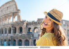 A woman is turning and looking over her shoulder while laughing, enjoying being a tourist in the beautiful city of Rome. In the background, the Colosseum. - stock photo