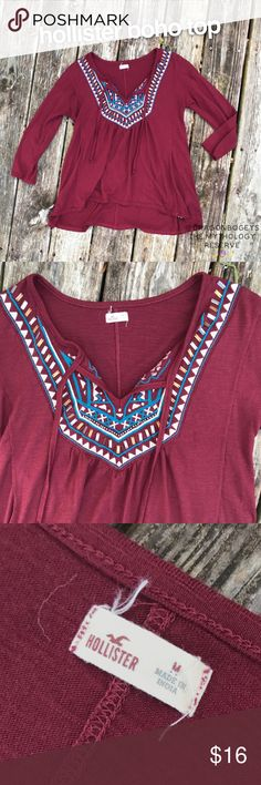 """Hollister Boho Top Dark burgundy red easy fit top with three quarter length sleeves and tie neckline. Teal and cream embroidery detailing at the neckline along with bronze and silver square beads. Slight high low hemline. Fabric is 70% polyester and 30% viscose. Length is 24"""", bust is 18.5"""" laid flat. Worn a few times, in excellent gently used condition. Hollister Tops"""