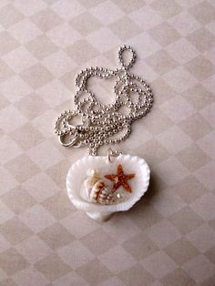 At the Beach Pendant - Sand, starfish, shell and faux pearls encased in resin on a seashell. $7.50, via Etsy.