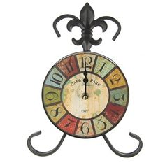 Looking for a functional, beautiful piece for your home or office? Look no further than this Metal Easel Table Clock!    This colorful clock features distressed shades of red, blue, green, turquoise and more, a distressed tan clock face, playful number markings, a black metal frame and fleur-de-lis accent, and a few stylish patterns like polka dots and florals. Place this stunning clock on the mantel or on a tabletop for an instant pop of color and an added dose of charm.       ...